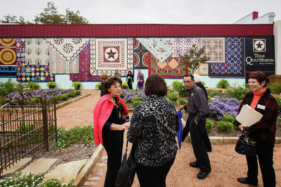 Visitors from the Pearl Fincher Museum of Fine Arts look walk through a period garden along with a large quilt mural at the Texas Quilt Museum, Friday, Oct. 26, 2012, in La Grange. Photo: Michael Paulsen, Houston Chronicle / © 2012 Houston Chronicle