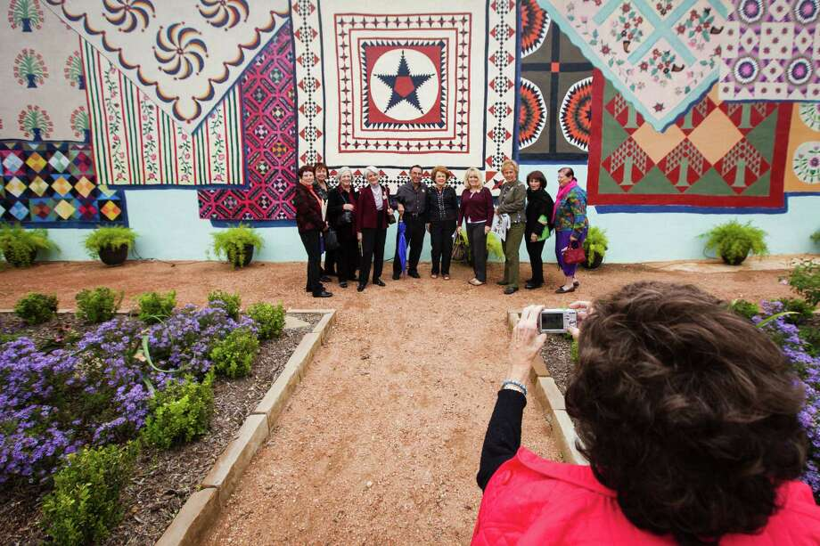Visitors from the Pearl Fincher Museum of Fine Arts have their photo taken near a large quilt mural at the Texas Quilt Museum, Friday, Oct. 26, 2012, in La Grange. Photo: Michael Paulsen, Houston Chronicle / © 2012 Houston Chronicle