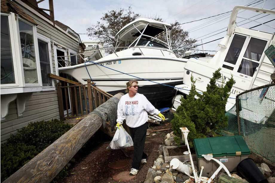 With boats piled up on her property by Superstorm Sandy, Regina Yahara-Splain of Highlands, N.J., joined millions of East Coast residents who are trying to cope with the damage from the hurricane. Photo: Andrew Burton, Stringer / 2012 Getty Images
