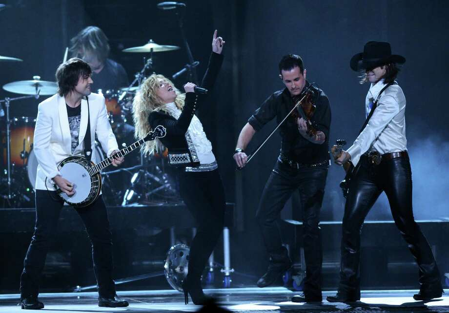 NASHVILLE, TN - NOVEMBER 01:  (L-R) Neil Perry, Kimberly Perry, and Reid Perry (far right) of The Band Perry perform during the 46th annual CMA Awards at the Bridgestone Arena on November 1, 2012 in Nashville, Tennessee. Photo: Jason Kempin, Getty Images / 2012 Getty Images