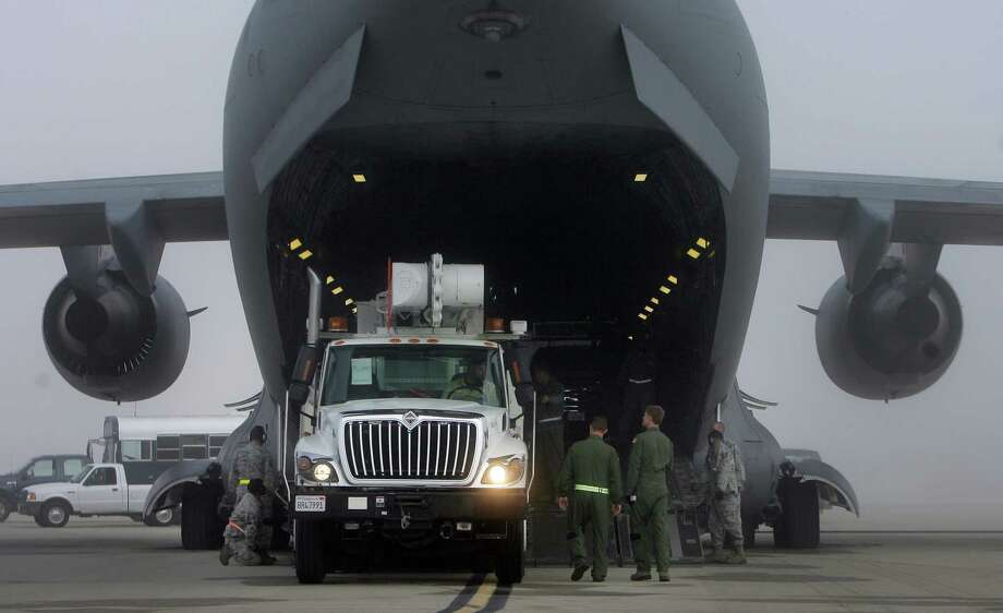 A utility truck is loaded Thursday onto a C-17A Globemaster III to be flown to New York. Photo: Stan Lim, MBR / The Press-Enterprise