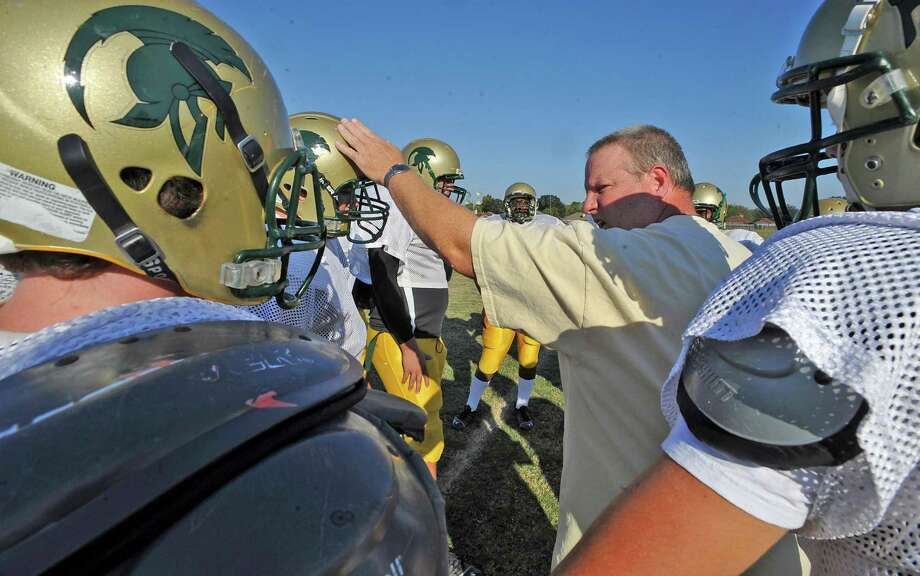 Legacy Christian Academy football coach Byron Sanford, center, is in his first year as the head coach and the team is trying to make the playoffs.   On Tuesday afternoon he was on the field with his team minus a couple of players due to grade problems. Here he gives instructions to his offensive players for the next play to run.  Dave Ryan/The Enterprise Photo: Dave Ryan