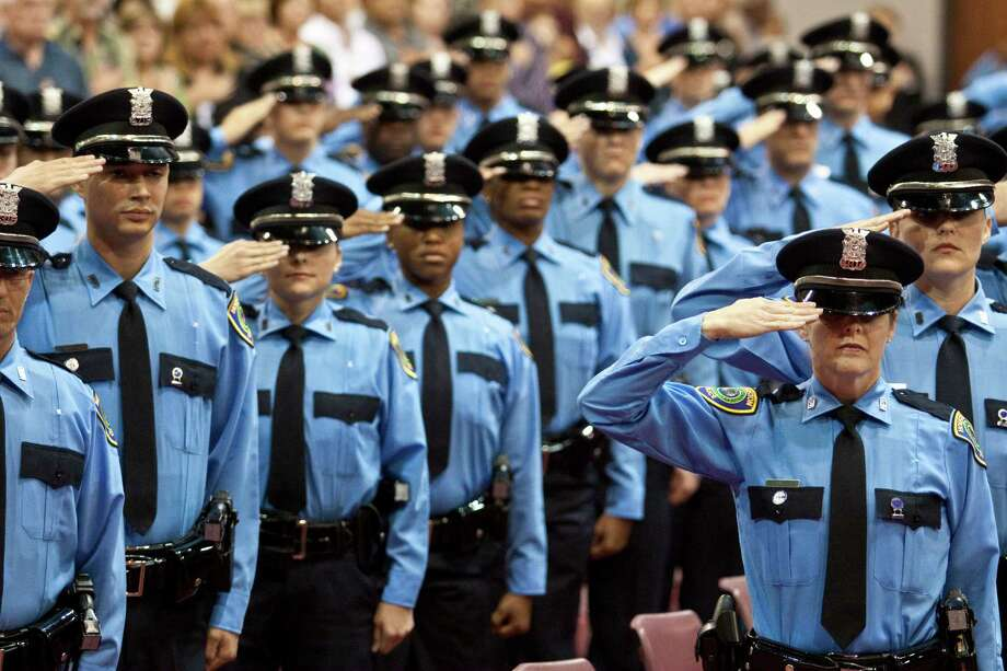 HPD graduates salute the flag in 2010. Councilman C.O. Bradford, a former police chief, says savings from a reduction in the number of cadets could pay for programs that would thwart gang membership. Photo: Eric Kayne, For The Chronicle / Freelance