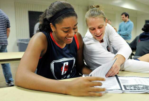 Connecticut's Morgan Tuck and Heather Buck laugh while looking at the media guide during their NCAA college basketball media day in Storrs, Conn., Tuesday, Oct. 16, 2012. (AP Photo/Jessica Hill) Photo: Jessica Hill, Associated Press / FR125654 AP