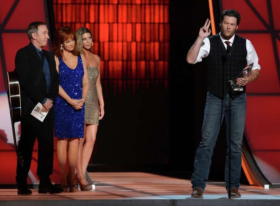 NASHVILLE, TN - NOVEMBER 01:  Blake Shelton (far right) accepts the award for Entertainer of the Year presented by (L-R) Tim Allen and Reba McEntire during the 46th annual CMA Awards at the Bridgestone Arena on November 1, 2012 in Nashville, Tennessee. Photo: Jason Kempin, Getty Images / 2012 Getty Images