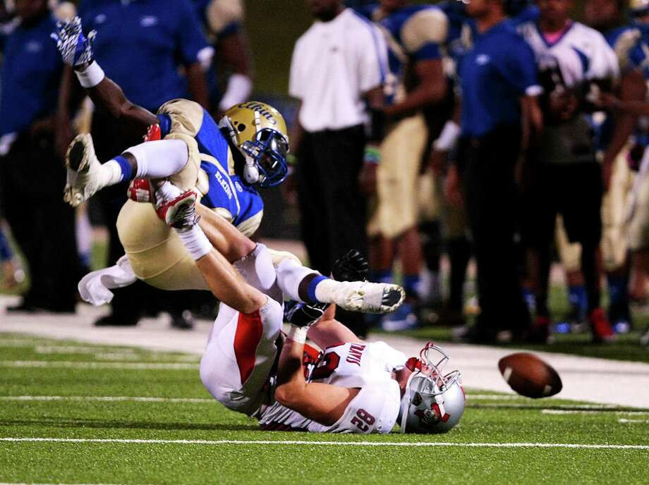 Elkins running back (32) Timothy Jackson fumbles after being tackled by Travis linebacker (82) Zach Hindt during the first half of Elkins High school and Travis High school district 23-5A match-up at Hall Stadium.  Thursday, Nov. 1, 2012, in Missouri City. Photo: Billy Smith II, Houston Chronicle / © 2012 Houston Chronicle