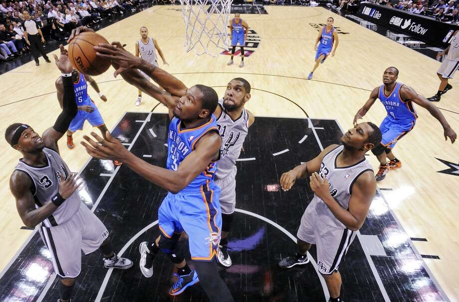 San Antonio Spurs' Stephen Jackson (from left) and San Antonio Spurs' Tim Duncan grab for a rebound against Oklahoma City Thunder's Kevin Durant as San Antonio Spurs' Boris Diaw looks on during first half action Thursday Nov. 1, 2012 at the AT&T Center. (Edward A. Ornelas / San Antonio Express-News)