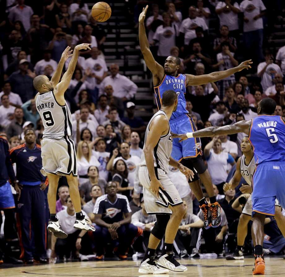 San Antonio Spurs' Tony Parker (9) shoots a buzzer-beating basket over Oklahoma City Thunder's Serge Ibaka, center, at the close of the fourth quarter of an NBA basketball game, Thursday, Nov. 1, 2012, in San Antonio. San Antonio won 86-84. Spurs' Tim Duncan, second from left, and Oklahoma City's Kendrick Perkins (5) watch. (AP Photo/Eric Gay) (Associated Press)