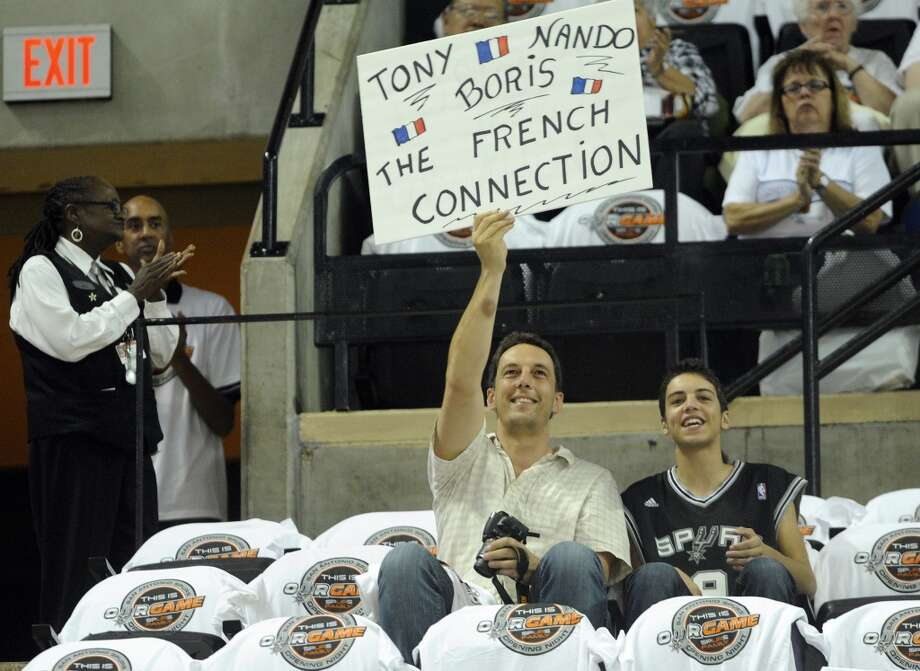 David Dupruex and his son, Alexander, who ventured to San Antonio from France to support the three French players on the San Antonio Spurs roster; Boris Diaw, Nando De Colo and Tony Parker, cheer as the players take the court before the Spurs' game against the Oklahoma City Thunder in the at the AT&T Center on Thursday, Nov. 1, 2012. The game was the home opener for the Spurs. (San Antonio Express-News)