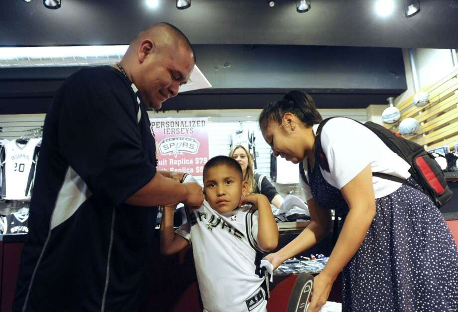 Keshaun Lopez receives help form his parents, Henderson and Chereen Lopez, as he tries on a San Antonio Spurs shirt at the AT&T Center at the AT&T Center on Thursday, Nov. 1, 2012. The game against Oklahoma City was the home opener for the Spurs. (Billy Calzada / San Antonio Express-News)