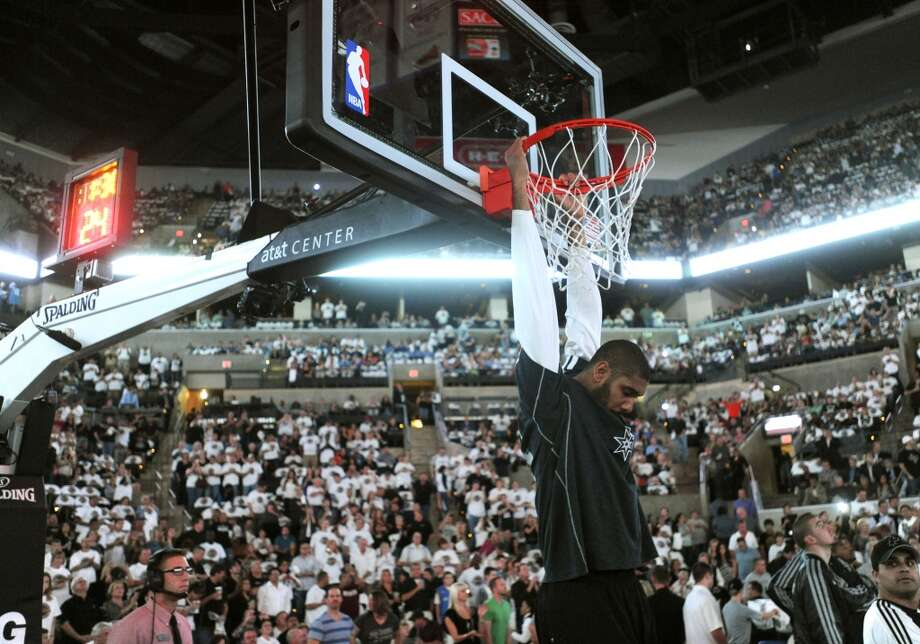 Spurs veteran forward Tim Duncan hangs from the rim, as he always does before team introductions, before the Spurs take on Oklahoma City in the home opener at the AT&T Center on Thursday, Nov. 1, 2012. (Billy Calzada / San Antonio Express-News)