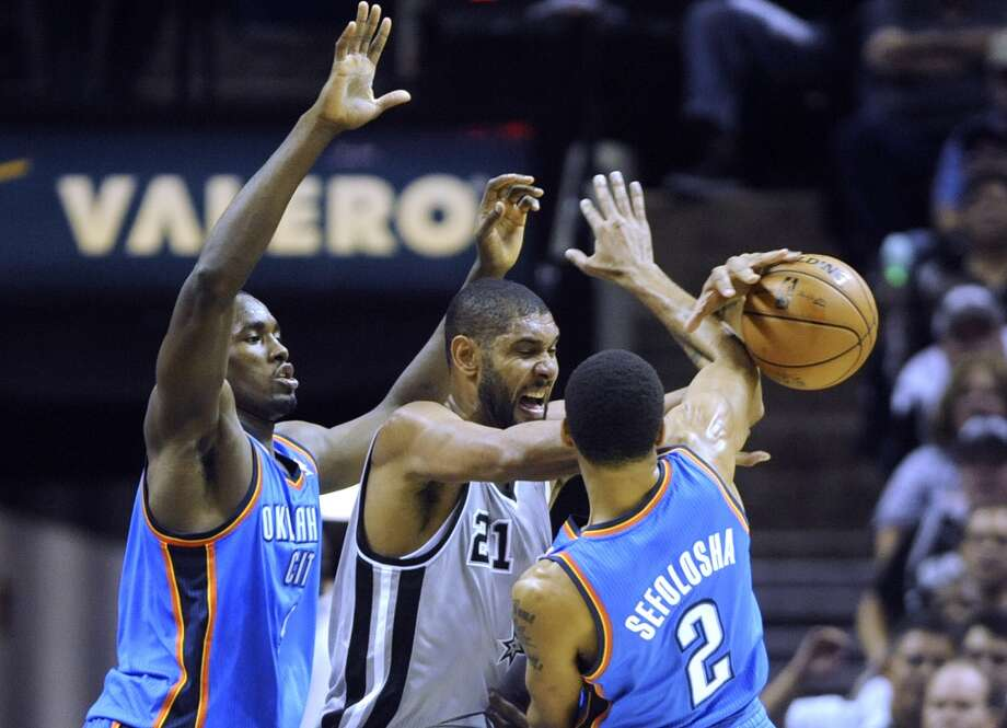 Tim Duncan of the San Antonio Spurs, middle, battles Serge Ibaba, left, and Thabo Sefolosha of the Oklahoma City Thunder during NBA action at the AT&T Center on Thursday, Nov. 1, 2012. The game was the home opener for the Spurs. (Billy Calzada / San Antonio Express-News)