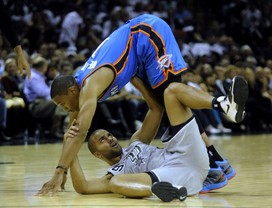 Tony Parker of the Spurs, bottom, gets tangled up with Russell Westbrook of the Oklahoma City Thunder during third-quarter NBA action at the AT&T Center on Thursday, Nov. 1, 2012. The game was the home opener for the Spurs. (Billy Calzada / San Antonio Express-News)