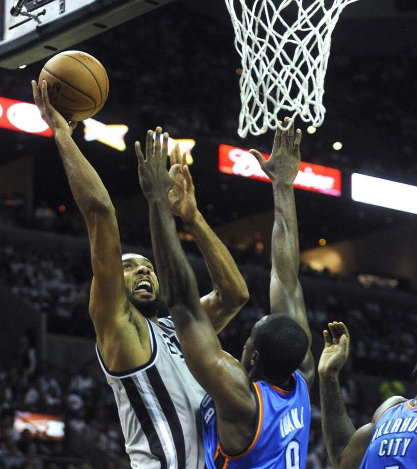 Tim Duncan of the Spurs scores over Serge Ibaka during third-quarter NBA action at the AT&T Center on Thursday, Nov. 1, 2012. The game was the home opener for the Spurs. (Billy Calzada / San Antonio Express-News)