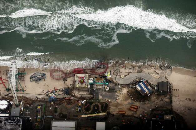 In this aerial photo, debris from an amusement park destroyed during Superstorm Sandy lines the beach in Seaside Heights, N.J. Thursday, Nov. 1, 2012.  The photo was taken during a flight to document coastal changes by the National Oceanic and Atmospheric Administration after the storm moved through the area. (AP Photo/Alex Brandon) Photo: Alex Brandon