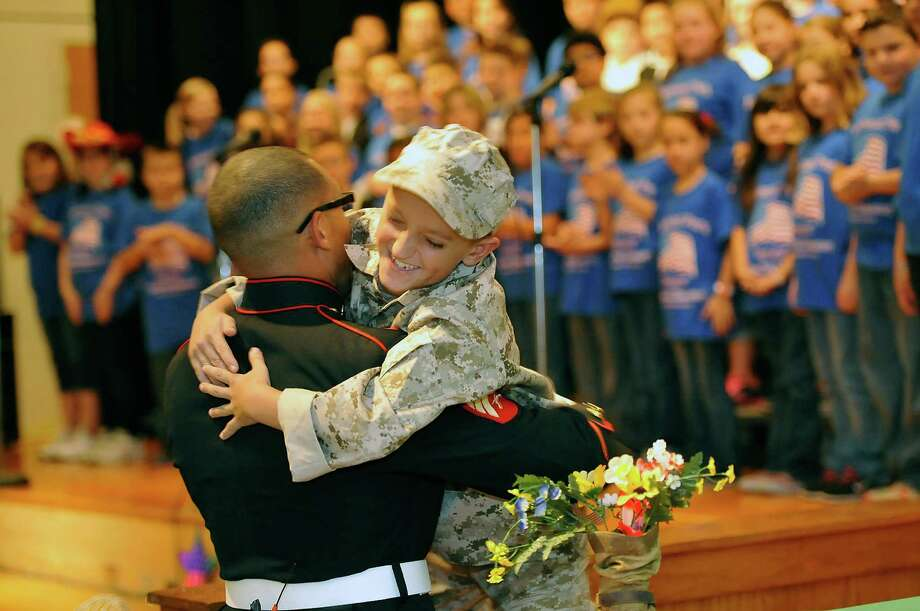 Fourth graders at Highland Park Elementary School in Nederland held a music program for veterans day Thursday, Nov. 1, 2012. One of the fourth-graders, Justice Kay, right, was surprised because his big brother, Sheridan Davis, left, came home from Afghanistan for a quick visit and came to the show without any notice to his little brother ahead of time. When the teacher made the announcement that Davis was in the audience, Justice came down off the stage and jumped into his big brother's arms.   Dave Ryan/The Enterprise Photo: Dave Ryan
