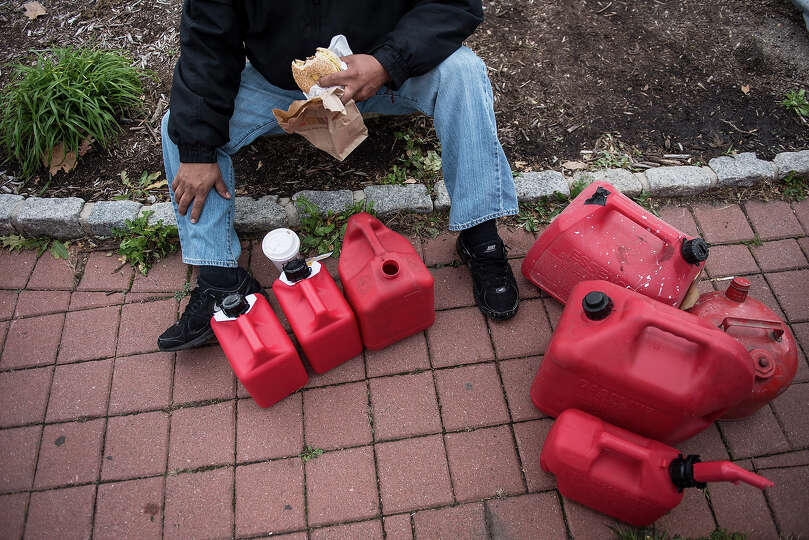 A man eats a sandwich while waiting with others in a line for fuel at a Shell Oil station on Novembe