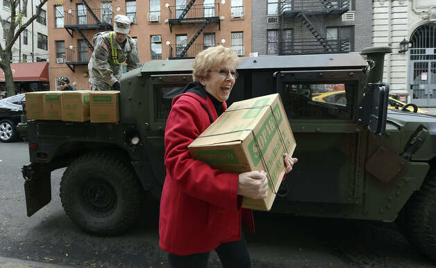 Workers with the The Father's Heart Ministry Center get a delivery of supplies from the New York City Coalition Against Hunger and US Army National Guard on November 1, 2012 as New Yorkers cope with the aftermath of Hurricane Sandy.  The storm left large parts of  York City without power and transportation. The   AFP PHOTO / TIMOTHY A. CLARY Photo: TIMOTHY A. CLARY, AFP/Getty Images / 2012 AFP
