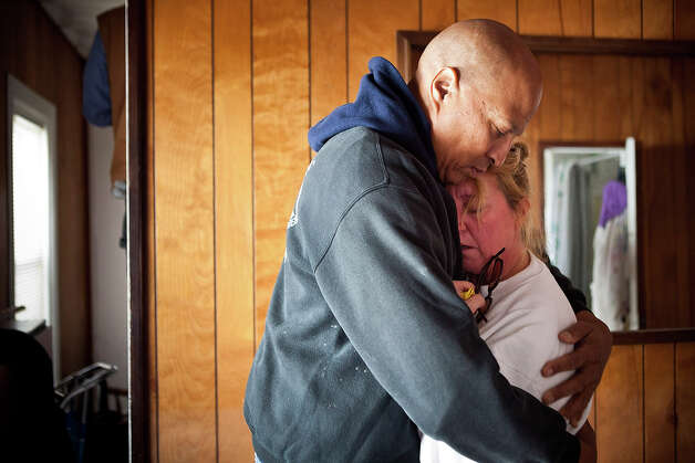 HIGHLANDS, NJ - NOVEMBER 01:  Clifford Seay (L) holds his girlfriend, Regina Yahara-Splain, while cleaning out her home, which was damaged by Superstorm Sandy on November 1, 2012 in Highlands, New Jersey. Superstorm Sandy, which has left millions without power or water, continues to affect business and daily life throughout much of the eastern seaboard. Photo: Andrew Burton, Getty Images / 2012 Getty Images
