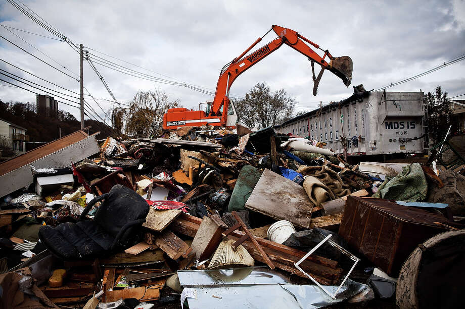 HIGHLANDS, NJ - NOVEMBER 01:  A hydraulic excavator dumps trash, aggregated into a central location after Superstorm Sandy destroyed numerous homes on November 1, 2012 in Highlands, New Jersey. Superstorm Sandy, which has left millions without power or water, continues to affect business and daily life throughout much of the eastern seaboard. Photo: Andrew Burton, Getty Images / 2012 Getty Images