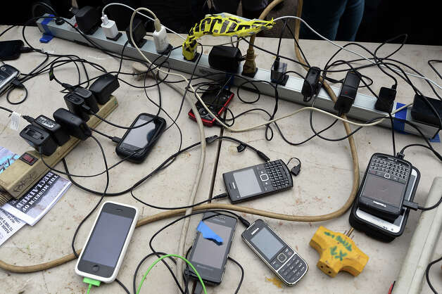 Cell phones plugged into power strips attached to a generator powered by two men on a tandem bicycle on Avenue C in the East Village  November 1, 2012 in New York as the city recovers from the effects of Hurricane Sandy. This neighborhood is in the area of Manhattan without any electrical power. The power station is in front of The Museum of Reclaimed Urban Space, which has postponed their scheduled opening this month due to the storm. AFP PHOTO/Stan HONDA Photo: STAN HONDA, AFP/Getty Images / 2012 AFP