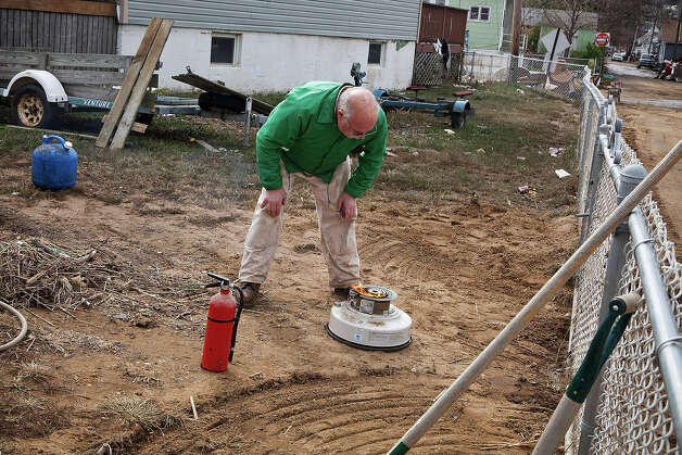 HIGHLANDS, NJ - NOVEMBER 01:  A man attempts to start a space heater that was recovered from his flooded home on November 1, 2012 in Highlands, New Jersey. Superstorm Sandy, which has left millions without power or water, continues to affect business and daily life throughout much of the eastern seaboard. Photo: Andrew Burton, Getty Images / 2012 Getty Images