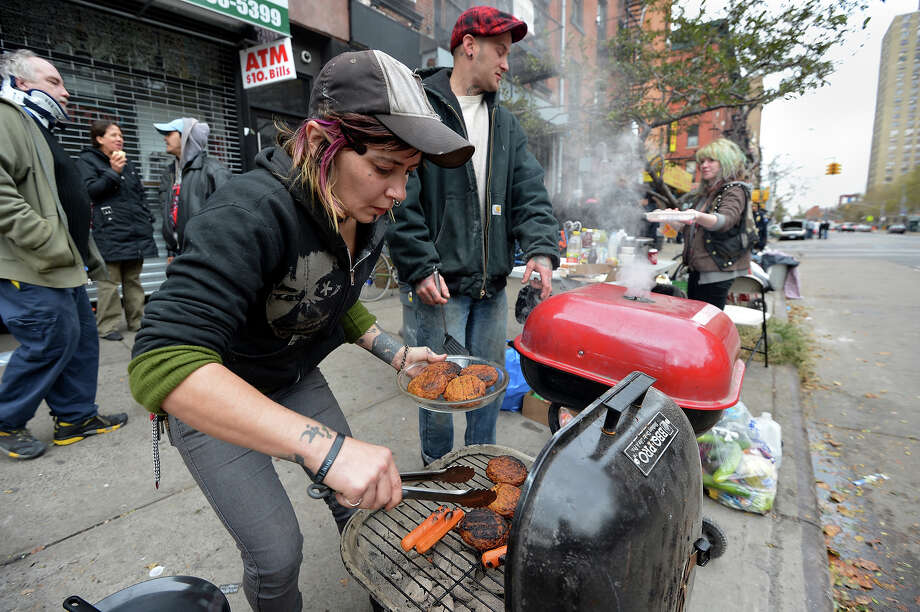 Nico Crowe cooks food to be given out to neighborhood residents on Avenue C in the East Village  November 1, 2012 in New York as the city recovers from the effects of Hurricane Sandy. Crowe and other residents live in the apartment building behind her and organized the food and a cell phone charging station since people are without power. Residents donated food that would spoil and voluntered to help distribute it. AFP PHOTO/Stan HONDA Photo: STAN HONDA, AFP/Getty Images / 2012 AFP