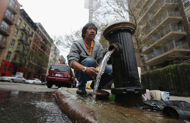 NEW YORK, NY - NOVEMBER 01: Public housing resident David (no last name given) washes dishes at an open fire hydrant outside his building in Manhattan's East Village following Superstorm Sandy on November 1, 2012 in New York City. David doesn't have power or water in his 16th-floor apartment, so he walks up and down the 16 flights daily to collect water from the hydrant. Some East Village residents are still without power or water and some of the public housing buildings in the area flooded during the storm. Photo: Mario Tama, Getty Images / 2012 Getty Images