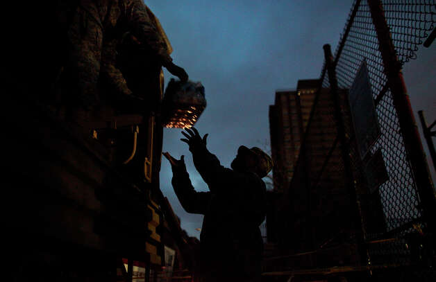 NEW YORK, NY - NOVEMBER 01: The Army National Guard unload water at a distribution center November 1, 2012 in New York City. Limited public transit has returned to New York. With the death toll continuing to rise and millions of homes and businesses without power, the U.S. east coast is attempting to recover from the effects of floods, fires and power outages brought on by Superstorm Sandy. Photo: Allison Joyce, Getty Images / 2012 Getty Images