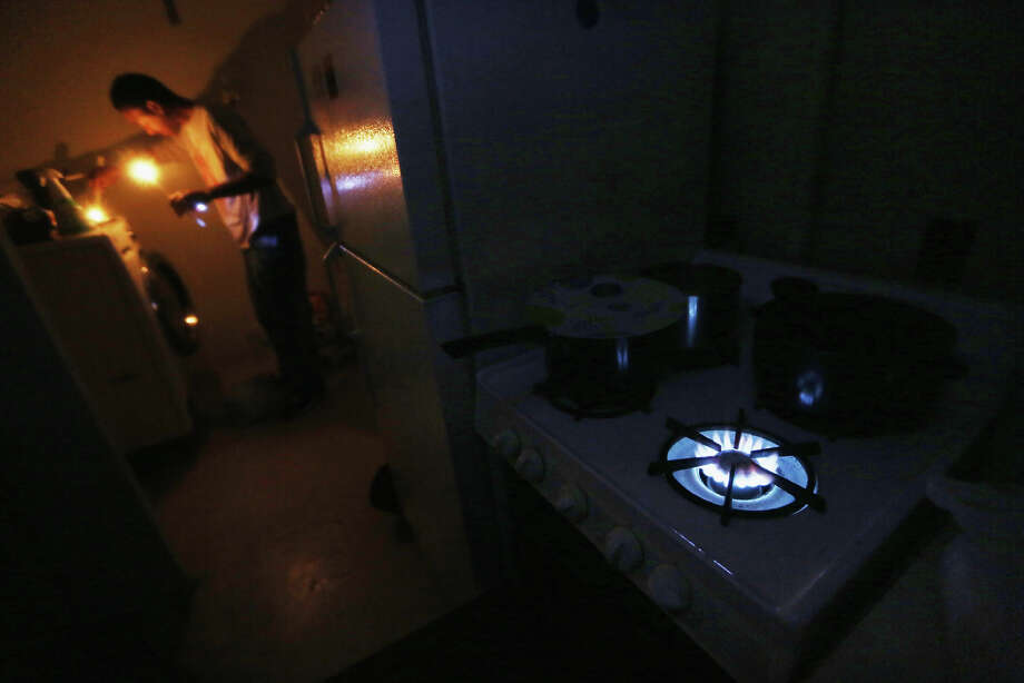 NEW YORK, NY - NOVEMBER 01: Geronimo Harrison stands in his apartment lit with candles and without power or water as the gas stove burns for heat in the Jacob Riis housing projects in Manhattan's East Village on November 1, 2012 in New York, United States. The residents of the 11th-floor apartment are using cooking gas for heat, must walk up and down eleven flights of dark stairs daily and have received virtually no governmental assistance since the storm struck. Residents of all the East Village housing projects have been without power and many without water since Superstorm Sandy hit, which flooded some of the housing projects. Photo: Mario Tama, Getty Images / 2012 Getty Images