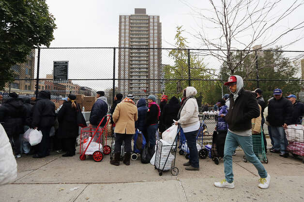 NEW YORK, NY - NOVEMBER 01: A man walks past as people line up to receive free necessities at a distribution point outside public housing units in Manhattan's East Village following Superstorm Sandy on November 1, 2012 in New York City. East Village residents are still without power and some of the public housing buildings in the area flooded during the storm. Photo: Mario Tama, Getty Images / 2012 Getty Images