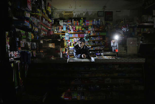 NEW YORK, NY - NOVEMBER 01: Park Choul waits behind the counter in his deli lit by flashlights in Manhattan's East Village following Superstorm Sandy on November 1, 2012 in New York City. Choul's deli remained open through the entire storm. East Village residents are still without power and some of the public housing buildings in the area flooded during the storm. Photo: Mario Tama, Getty Images / 2012 Getty Images