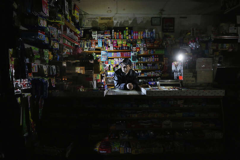 NEW YORK, NY - NOVEMBER 01: Park Choul waits behind the counter in his deli lit by flashlights in Ma