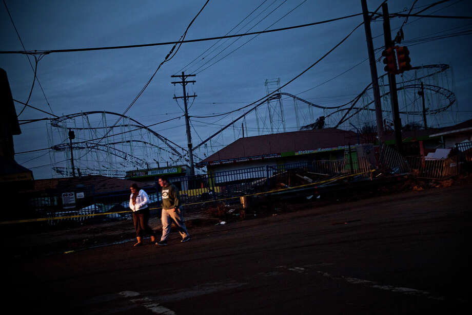 KEANSBURG, NJ - NOVEMBER 01:  A couple walks past the remains of the Keansburg Amusement Park after Superstorm Sandy swept across the region, on November 1, 2012 in Keansburg, New Jersey. Superstorm Sandy, which has left millions without power or water, continues to effect business and daily life throughout much of the eastern seaboard. Photo: Andrew Burton, Getty Images / 2012 Getty Images