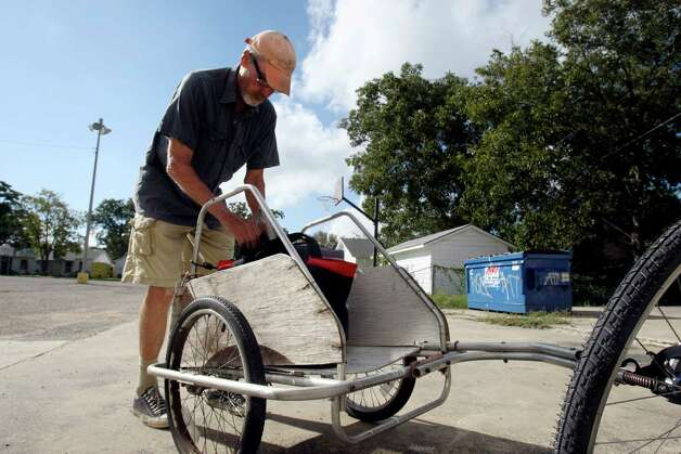 Jack Elder loads insulated carriers into the small trailer he pulls with his bicycle to deliver lunches for Meals on Wheels. Photo: Helen L. Montoya, San Antonio Express-News / ©SAN ANTONIO EXPRESS-NEWS