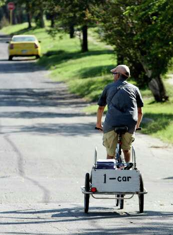 One less car on the road is the message on Jack Elder's bicycle trailer, which he rides around the East Side delivering lunches to elderly San Antonians. Photo: Helen L. Montoya, San Antonio Express-News / ©SAN ANTONIO EXPRESS-NEWS