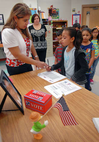 Second grade teacher Laura Vasquez helps students sign in during Kids Vote at Pena Elementary in Brownsville. Photo: Brad Doherty, Associated Press / The Brownsville Herald