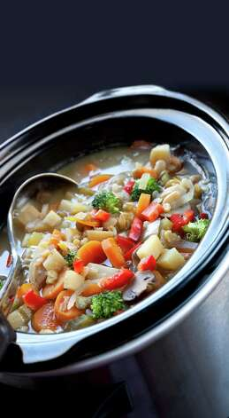 Vegetable soup, slow-cooked in a crock pot, ready to serve.