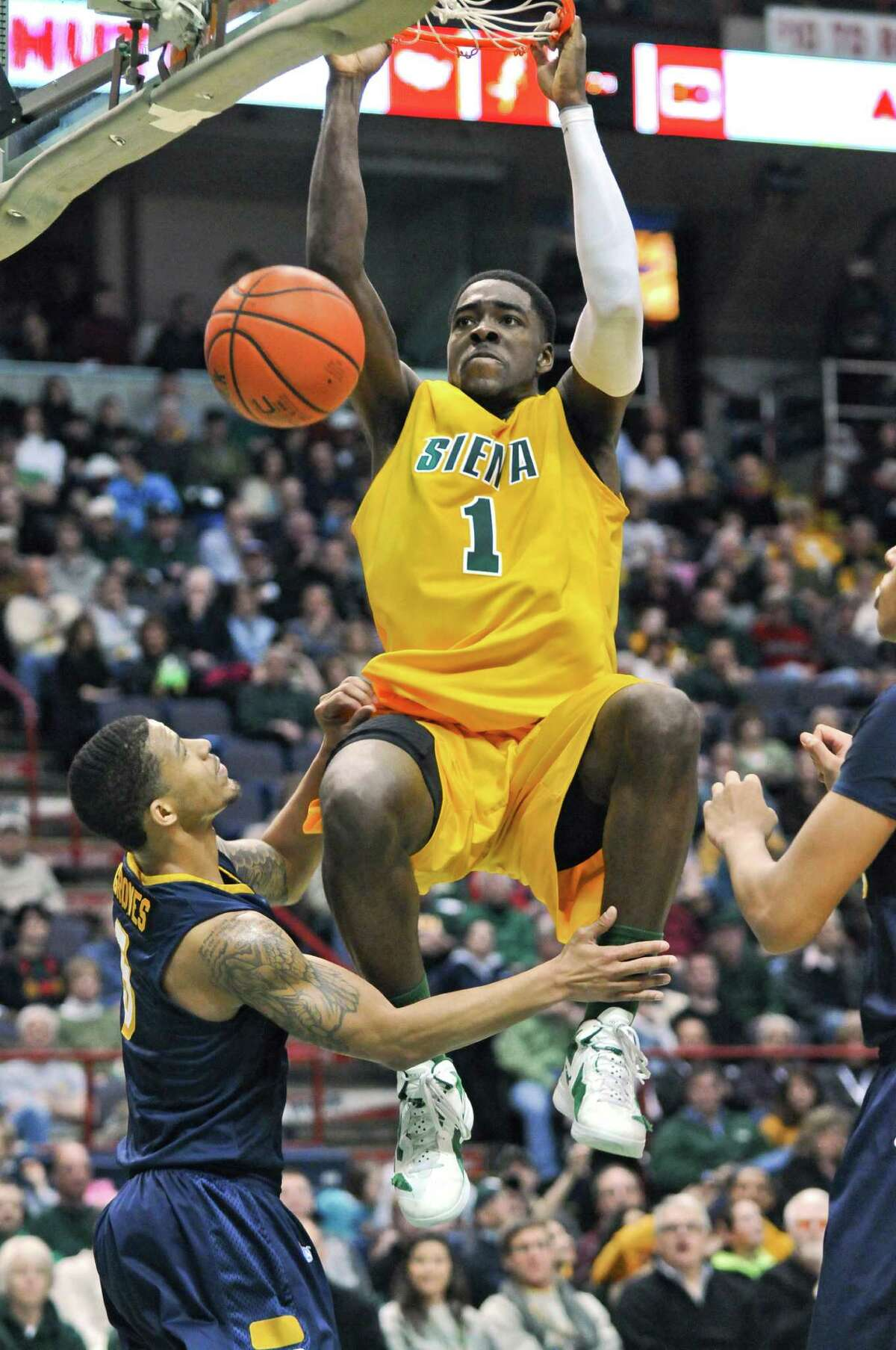 Siena's OD Anosike jams home a rebound over Canisius Reggie Groves during the second half of Siena's 86-75 victory at the Times Union Center on Sunday Feb. 26, 2012 in Albany, N.Y. (Philip Kamrass / Times Union )