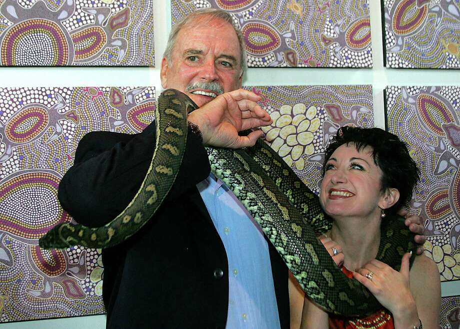 "Turns out John Cleese lobbies to protect endangered animals. Here he is wrapped up in a python at Sydney, Australia's Taronga Zoo on Jan. 6, 2009., Next to him is Caroline O'Connor, described as ""Australia's leading lady of song and dance."" No word on whether the snake had eaten a parrot -- a Norwegian blue pining for the fjords, perhaps.   AFP PHOTO/Torsten BLACKWOOD Photo: TORSTEN BLACKWOOD, Getty / 2006 AFP"