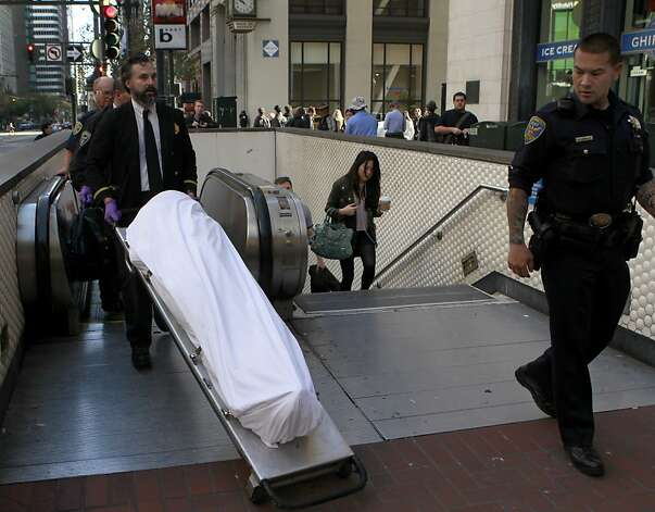 Authorities remove the body of a man killed on the tracks near Montgomery Station. Muni was partly shut down for almost three hours after the fatality. Photo: Paul Chinn, The Chronicle
