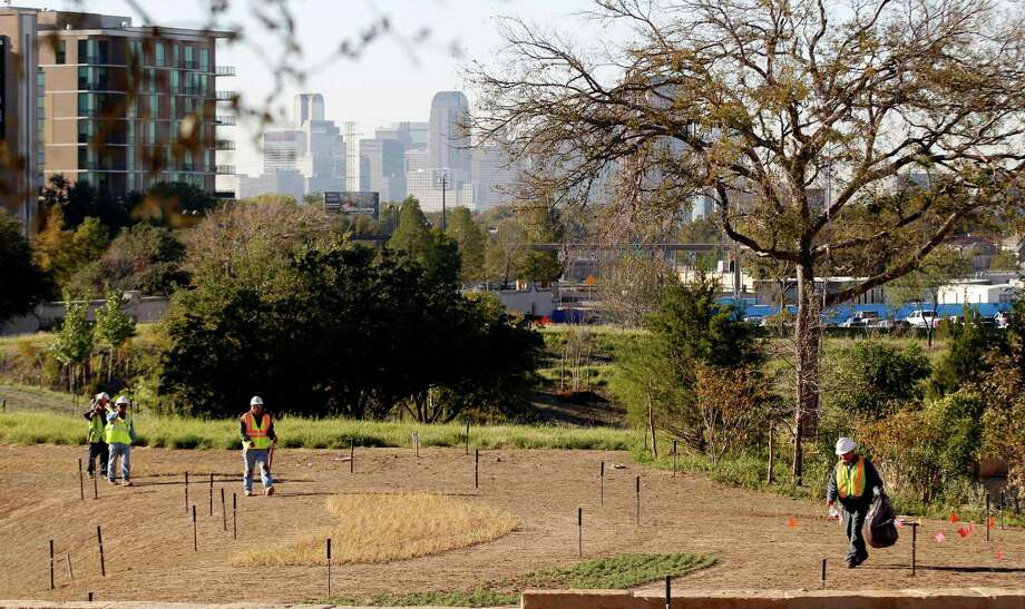 """Workers cross a mini prairie at the George W. Bush Presidential Center in Dallas. A 15-acre park at the center will re-create a Texas prairie. """"It'll be the most attractive because it's suitable for this kind of weather, this climate that we have in Dallas,"""" says Laura Bush. Photo: L.M. Otero, Associated Press / AP"""