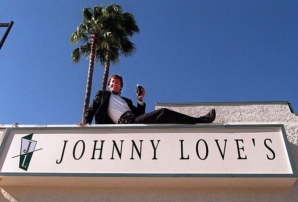 JOHNNY METHENY, SITS ATOP THE RESTAURANT SIGN. JOHNNY LOVE ATOP HIS NEW PLACE IN WALNUT CREEK in 1995.