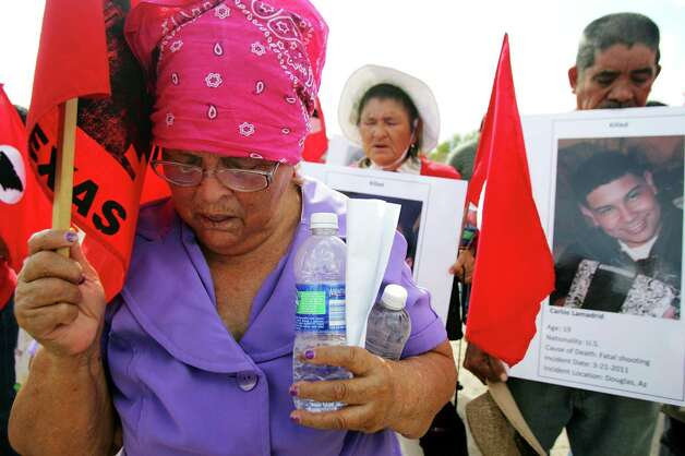 Margarita Ibarra prays as members of LUPE gather during a news conference and vigil Thursday Nov. 1, 2012, on the corner of Farm-to-Market Road 2221 and Mile 7 near La Joya, Texas. The Texas trooper who fired on a fleeing pickup truck from a helicopter near the U.S.-Mexico border, killing two illegal immigrants hiding in the bed, has returned to work but in a different role, the state Department of Public Safety said Thursday. The announcement came less than an hour after the American Civil Liberties Union and local civil rights organizations gathered near the site of the Oct. 25 shooting to demand an investigation by an independent body outside the agency. Photo: The Monitor, Gabe Hernandez