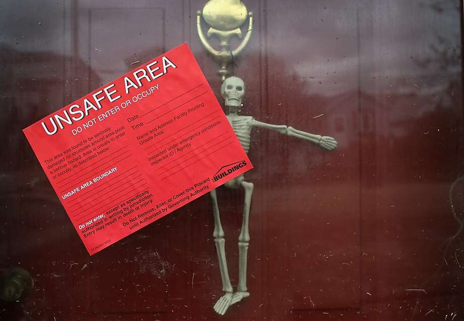 Stay away:A red card, ironically placed over a Halloween decoration, hangs on the front door of a condemned house in the Ocean Breeze area of the Staten Island. Most homes in the seaside community were inundated by the ocean surge caused by Superstorm Sandy. Photo: John Moore, Getty Images