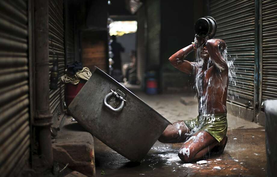 Tub of suds:An Indian laborer bathes in an alley near a market in New Delhi. Photo: Altaf Qadri, Associated Press