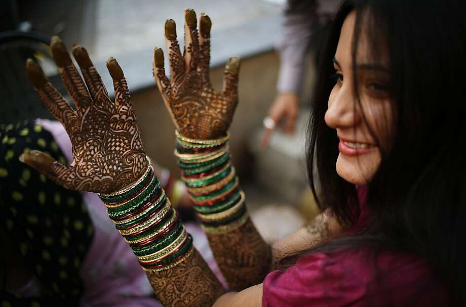 Holiday for husbands:An Indian Hindu woman dries her henna-decorated hands ahead of the Karwa Chauth festival in New Delhi. During Karwa Chauth, married women fast one day and offer prayers to the moon for the welfare, prosperity and longevity of their husbands. Photo: Saurabh Das, Associated Press