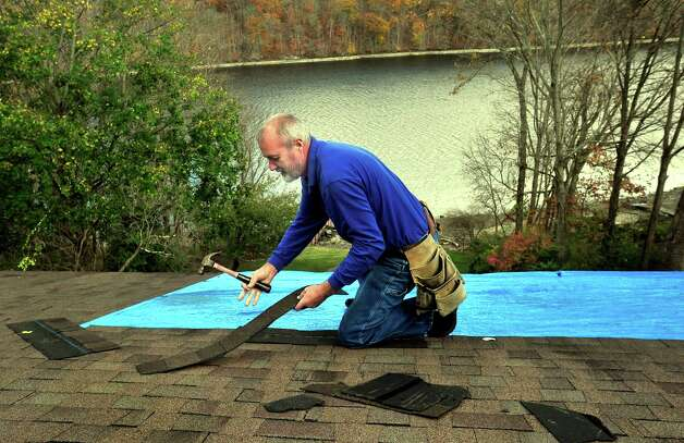 Kurt Carl Berg repairs his Brookfield neighbor's roof after Hurricane Sandy ripped a section off. Photographed Friday, Nov. 2, 2012. Photo: Michael Duffy / The News-Times