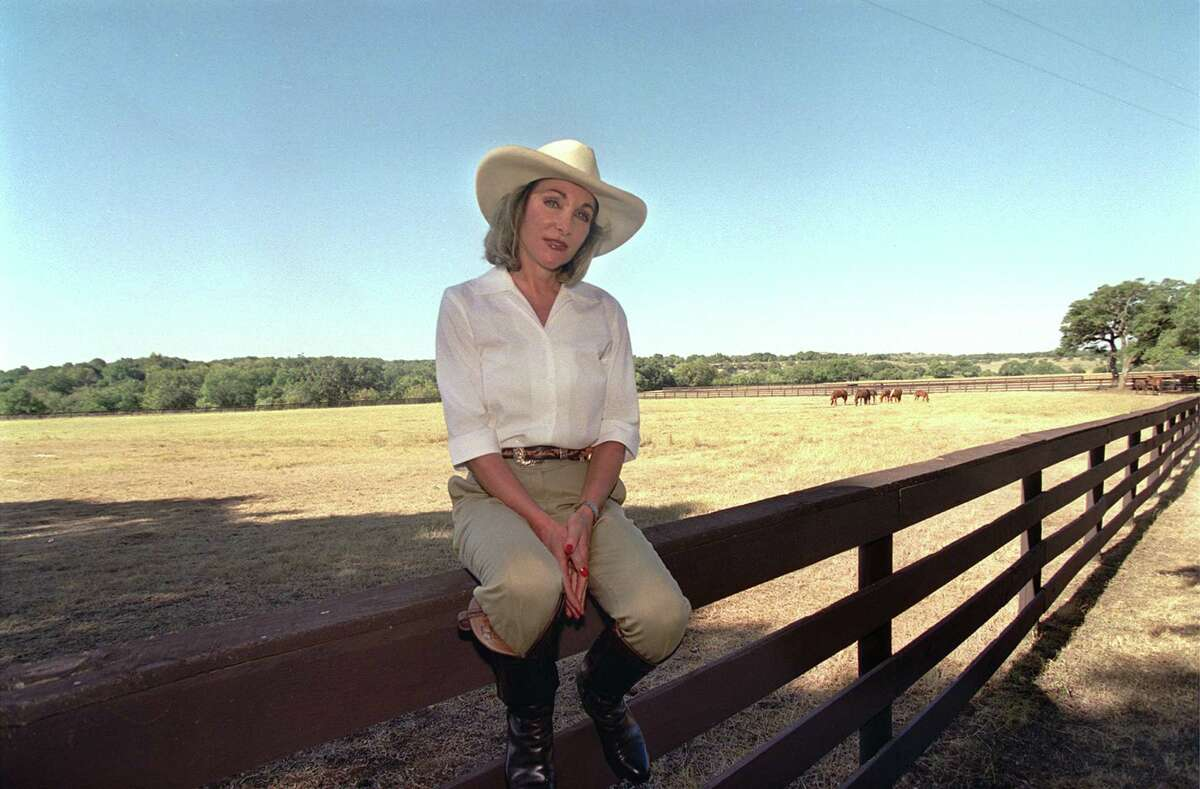Julianna Holt relaxes on a fence line at her ranch Near Blanco on August 27, 2001.