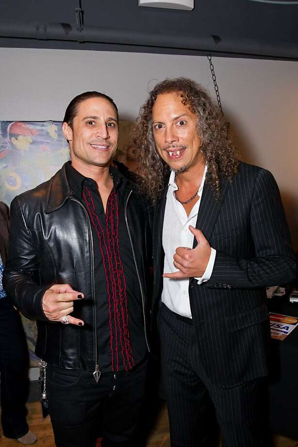 """Metallica guitarist Kirk Hammett (right) wears fangs to a launch of his new book, """"Horror Business,"""" and Day of the Dead party at Public Works nightclub on Nov. 1, coordinated by club promoter Sebastien (at left.) Hammett said he wanted to share his collection with other """"horror nerds"""" of the world. What makes something collectible? """"If it moves you, it's a collectible, if you feel passionate about it, it's a collectible. You can't collect wrong."""" Photo: Drew Altizer Photography"""